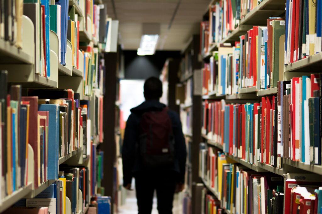 een jongen staat tussen twee boekenkasten
